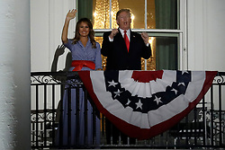 U.S. President Donald Trump and First Lady Melania Trump react from a balcony of the White House during a fireworks display in Washington, D.C., U.S., on Wednesday, July 4, 2018. Trump's campaign won the technical knockout of a lawsuit filed by two Democratic National Committee donors and a DNC staffer who accused it of colluding with Russian to publish compromising information about the Clinton campaign on WikiLeaks that included details about their lives. Photographer: Yuri Gripas/Bloomberg