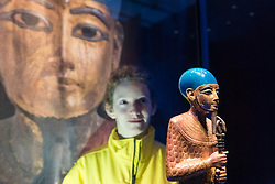 """© Licensed to London News Pictures. 01/11/2019. LONDON, UK. A staff member views """"Gilded Wooden Statue of Ptah"""".  Preview of """"Tutankhamun, Treasures of the Golden Pharoah"""" at the Saatchi Gallery in Chelsea.  The exhibition celebrates the 100th year anniversary of the opening of Tutankhamun's tomb and displays 150 works in the largest collection of Tutankhamun's treasures ever to leave Egypt.  The show runs 2 November to 3 May 2020.  Photo credit: Stephen Chung/LNP"""
