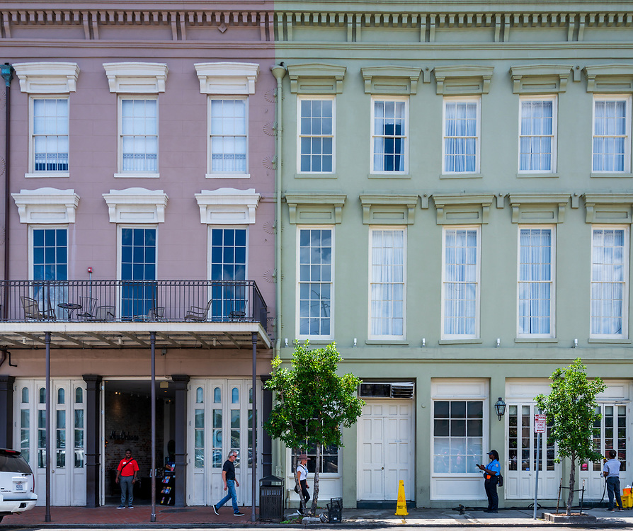 New Orleans, LA, USA -- May 23, 2019.  Tourists down a street against a backdrop of the architecture of the French Quarter in New Orleans; a police wo