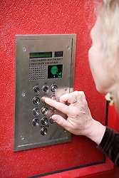 Woman pressing the buttons of a secure entry system,
