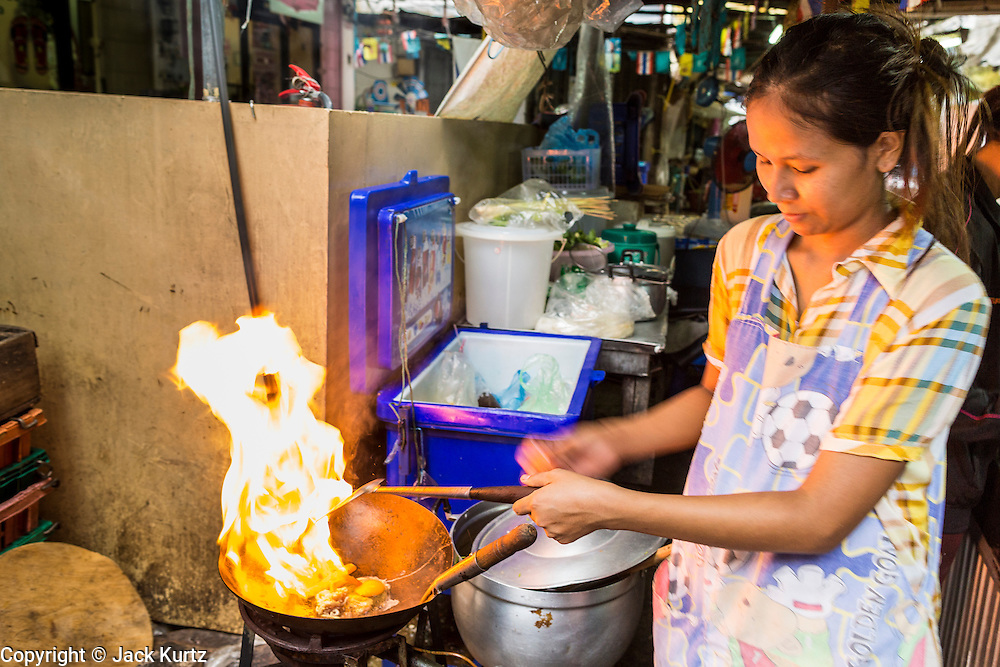 27 APRIL 2013 - BANGKOK, THAILAND:   A woman cooks at a street food stall in a market in Talat Noi. The Talat Noi neighborhood in Bangkok started as a blacksmith's quarter. As cars and buses replaced horse and buggy, the blacksmiths became mechanics and now the area is lined with car mechanics' shops. It is one the last neighborhoods in Bangkok that still has some original shophouses and pre World War II architecture. It is also home to a  Teo Chew Chinese emigrant community.         PHOTO BY JACK KURTZ