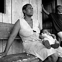 An Afro Colombian family on the banks of the Rio Atrato in Choco, Colombia. They are some of the countries more than 2 million internally displaced. The jungle area around their village is being fought over by both leftwing rebel groups and rightwing paramilitaries. The inhabitants of many villages have fled to Bellavista. This town was the site of a massacre in May 2002 when a homemade mortar fired by FARC rebels exploded on the roof of a church and killed 119 civillians hiding inside.<br />
