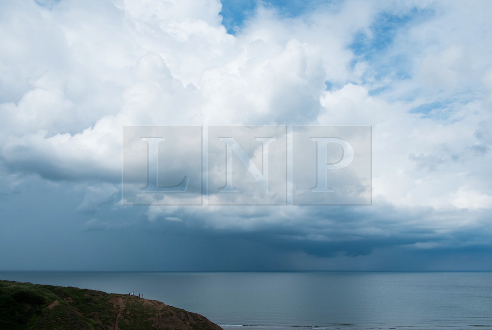 © Licensed to London News Pictures. <br /> 06/08/2014. <br /> <br /> Saltburn by the Sea, United Kingdom<br /> <br /> Four friends walk along the ridge of a hill in Saltburn by the Sea in Cleveland as storm clouds build further out in the North sea.<br /> <br /> Photo credit : Ian Forsyth/LNP