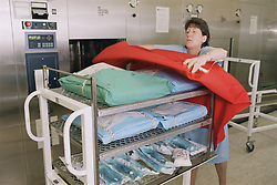 Autoclave Attendant from sterile services preparing trolley,