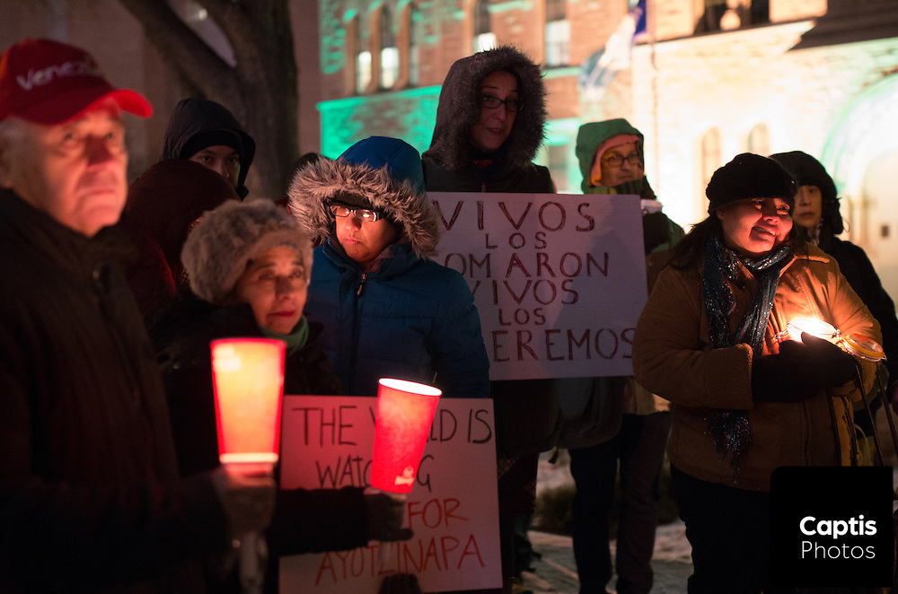 People hold candles and signs during a vigil for 43 missing Mexican students. November 20, 2014.