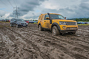 This AA land rover was stuck for several minutes while attempting to tow a members car passed that of a non member - Festival prepare to leave the festival. AA vans have had to pull cars out of the mud and conditions for pedestrians and cars, alike, are very muddy (heavy going) on the morning of the final day of the festival after days of rainy weather.The 2016 Glastonbury Festival, Worthy Farm, Glastonbury.