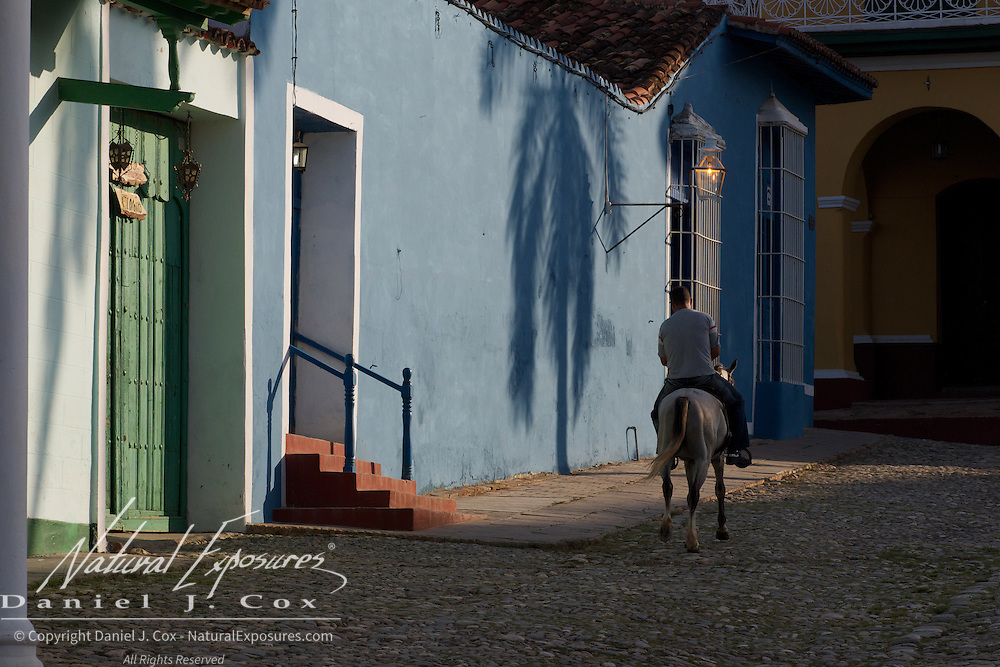 A local resident of Trinidad rides his horse up one of the side streets. Cuba.