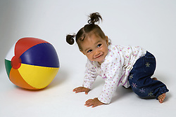 Baby crawling towards beach ball on the floor,