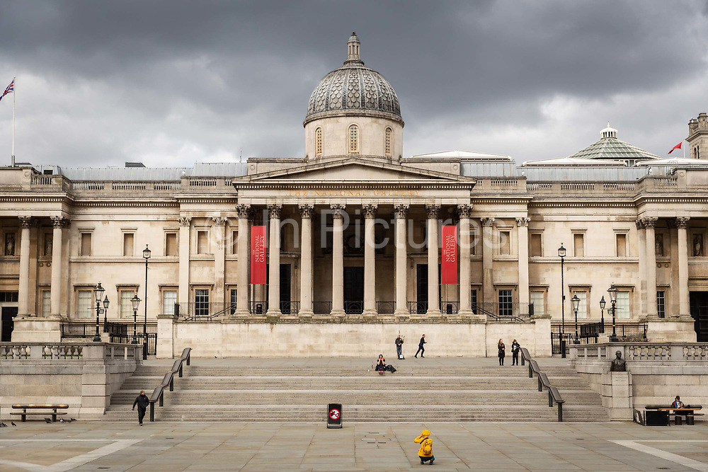 A woman kneels to take a photograph of the empty steps in front of the National Gallery in Trafalgar Square in London on March 20th, 2020. The centre of London is extremely quiet after the numbers of tourists has plummeted and locals limit their activities due to the Coronavirus crisis. .