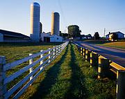 Sunrise illuminating silos and fence along farm on Highway 557 west of Berlin, Ohio.