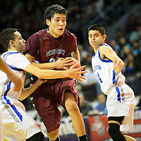 031214  Adron Gardner/Independent<br /> <br /> Shiprock Chieftain Justin Begay (20) tucks the ball on a drive against the St. Michael's Horsemen during the state high school basketball tournament at the Santa Ana Star Center in Rio Rancho Tuesday.