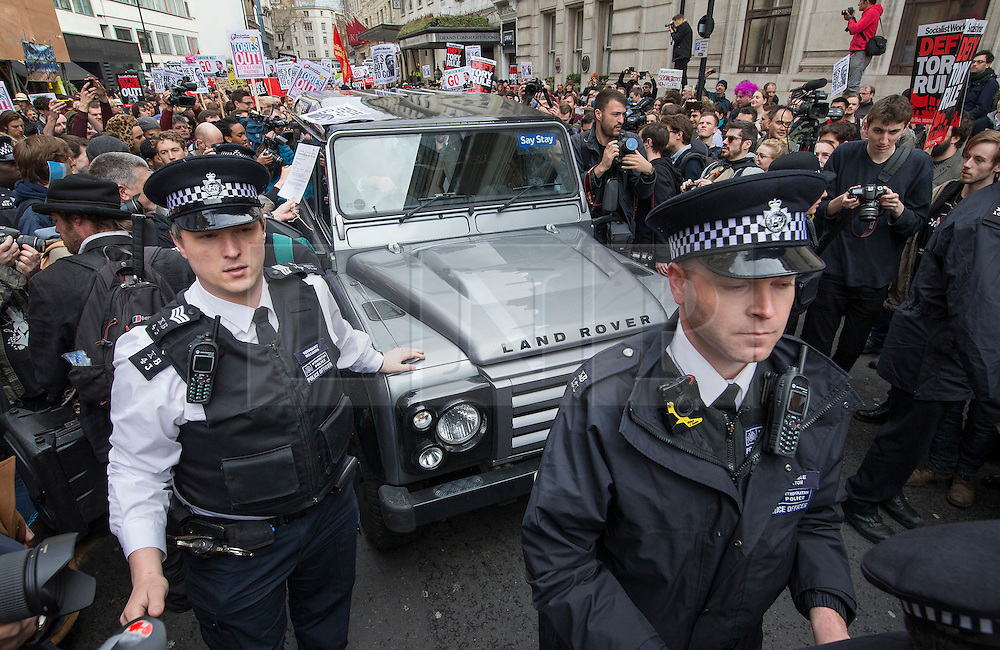 © Licensed to London News Pictures. 09/04/2016. London, UK. Police escort a Conservative supporter in his Land Drover as it is surrounded by tax reform demonstrators at the Conservative Spring Conference at the Connaught Rooms. Photo credit: Peter Macdiarmid/LNP