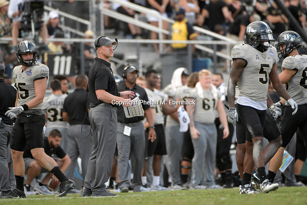 Central Florida head coach Scott Frost, center, instructs the team from the sideline during the second half of the American Athletic Conference championship NCAA college football game against Memphis Saturday, Dec. 2, 2017, in Orlando, Fla. Central Florida won 62-55. (Photo by Phelan M. Ebenhack)