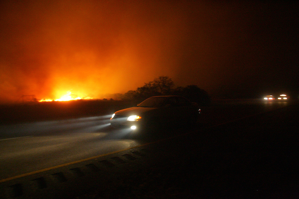 San Manuel, TX - 18 Mar 2008 -.A car races down US 281 just before it was shut down as a large fire bears down from the west on Tuesday evening..Photo by Alex Jones / ajones@themonitor.com