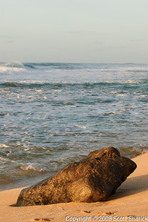A large rock sits on the beach on the North Shore of Oahu, Hawaii.