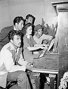 """Ackroyd 00053-76. """"Mexican Fiesta. Dayton, Oregon. September 15, 1945"""" caption published in Oregonian 9/17/1945 """"MUSIC. Four youths from south of the border sing some of the songs of old Mexico as they celebrate their country's independence day, Sept. 16, with countrymen at Dayton Sunday. Mrs. Dorothy Johnson plays piano."""""""