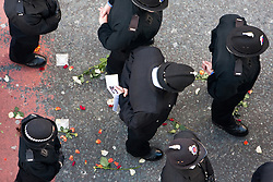 © Licensed to London News Pictures. 03/10/2012. Manchester, UK . Police stand in the wake of the cortege , the road beneath them strewn with flowers . 100s of police and public line Deansgate in Manchester City Centre for the funeral of PC Nicola Hughes at Manchester Cathedral . Hughes was murdered in a gun and grenade attack alongside PC Fiona Bone when responding to a suspected burglary at a house in Hattersley in Tameside on 18th September . Dale Cregan is currently on remand , accused of their murder . Photo credit : Joel Goodman/LNP