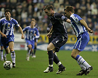 Photo: Dave Howarth.<br /> Wigan Athletic v Bolton Wanderers. Carling Cup.<br /> 20/12/2005.  Kevin Nolan (l) and Matt Jackson battle for the ball