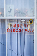 A Merry Christmas message and a Neighbourhood Watch sticker in the sash window of a Victorian terraced house in Herne Hill, SE24, on 18th December 2017, in London, England.