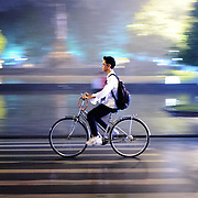 A young man rides a bicycle on  street in Hanoi's Old Quarter at night with motion blur.