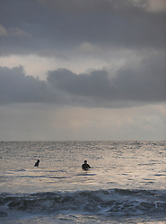 © Licensed to London News Pictures. 27/03/2014<br /> <br /> Cleveland, England<br /> <br /> Surfers on the north east coast of England sit and wait for waves as they enjoy an early morning surf.<br /> <br /> Photo credit : Ian Forsyth/LNP