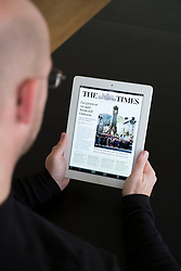 Man reading online mobile version of The Times newspaper on iPad 3 tablet computer