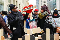 © Licensed to London News Pictures. 31/12/2016. Chicago, USA. A Peace March, organised by Father Michael Pfleger, takes place down Chicago's Magnificent Mile, Michigan Avenue, to honour the survivors and victims of the city's escalating gun violence.  Marchers carry a 2-foot-tall white wooden cross, each bearing the name of a person killed by gun violence in 2016.  With over 4,300 shootings and more than 750 people killed in 2016, these are the highest totals for 20 years and more than any other large U.S. city in 2016, according to news reports. Photo credit : Stephen Chung/LNP