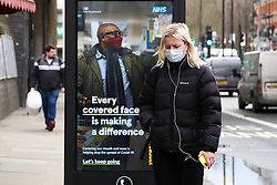 © Licensed to London News Pictures. 06/03/2021. London, UK. A woman wearing a protective face covering walks past the government's 'Every covered face is making a difference' awareness poster in north London.  The roadmap for the gradual reopening of the Covid-19 lockdown restrictions in England begins from Monday 8 March 2021. Primary and secondary schools will be the first to reopen in England, as the 'stay at home' guidance will change from 29 March 2021. Photo credit: Dinendra Haria/LNP