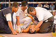 02 JULY 2006 - PHNOM PENH, CAMBODIA: Medics and officials check out a fighter after he lost in a knockout during a traditional Khmer boxing match in Phnom Penh, Cambodia. Khmer boxing is the same sport as Muay Thai (traditional Thai kick boxing) but because off animosity between Thailand and Cambodia it is called Khmer Boxing in Cambodia. The Cambodians claim to have invented the sport, which is also practiced in Laos and Burma. Photo by Jack Kurtz