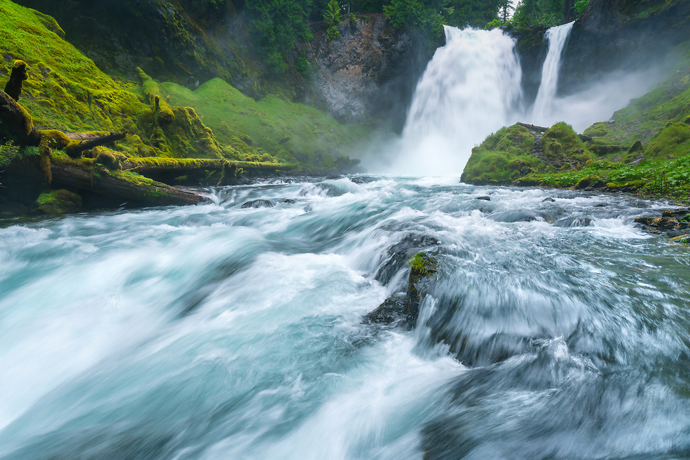 The ice-blue waters of the McKenzie River plummet over Sahalie Falls, in the Cascade Range of Oregon.