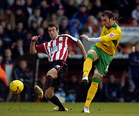 Photo: Jed Wee.<br />Sheffield United v Norwich City. Coca Cola Championship.<br />26/12/2005.<br />Norwich's Dean Ashton (R) fires a shot in on goal as Sheffield United's Michael Tonge looks on.