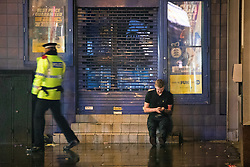 """© Licensed to London News Pictures . 23/12/2017. Manchester, UK. A police officer checks on a man's welfare on High Street . Revellers out in Manchester City Centre overnight during """" Mad Friday """" , named for being one of the busiest nights of the year for the emergency services in the UK . Photo credit: Joel Goodman/LNP"""