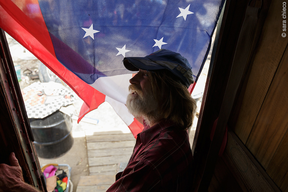 Paul Lineberger stands in the doorway of Jimmy Ray Silva's bus/home, adorned with an American flag. The year-round residents of Slab City fall into two fairly opposed groups when it comes to patriotism and government - fueled in large part by their military backgrounds. There's the pro-America with a deep love of this country end of the spectrum, and the anti-government, anti-intervention side.