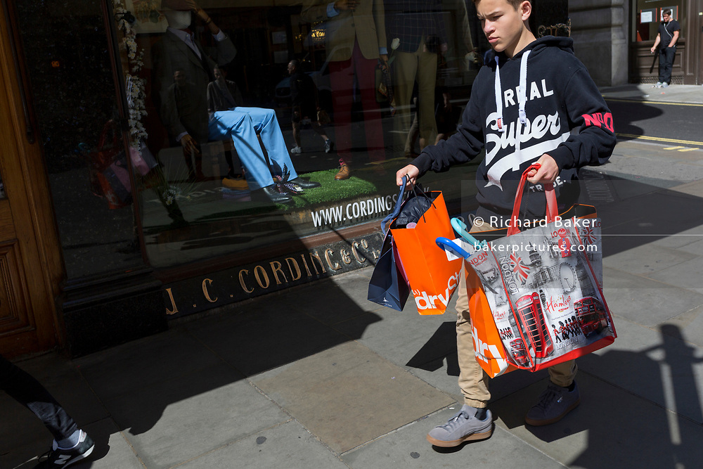 A young consumer clutches shopping bags from the retail brand Superdry, on 18th April 2017, in London, England.