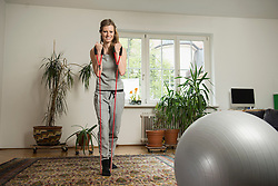 Young woman doing exercise with rope in living room, Munich, Bavaria, Germany