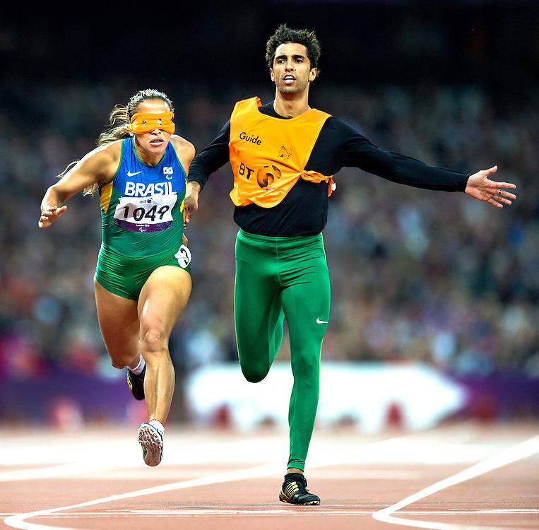 Engeland, Londen, 02-09-2012.<br /> Paralympische Spelen.<br /> Atletiek, Vrouwen, 100 meter T11, Finale.<br /> De blinde Guilhermina Terezinha ( nr. 1049 ) wint goud aan de hand van begeleider Guilherme Soares de Santana.<br /> Foto : Klaas Jan van der Weij