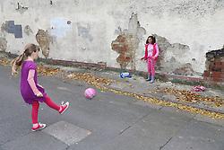 Girls playing football in street