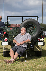 © Licensed to London News Pictures. 19/08/2017. Biggin Hill, UK. The owner of an historic Austin Champ military vehicle takes a nap in the sunshine at the Biggin Hill Festival of Flight 2017. The two day festival takes place in the centenary year of the historic airport. The Red Arrows will be flying along with a Belgian F-16, the Czech Air Force,  a Spitfire and a Typoon. Photo credit: Peter Macdiarmid/LNP