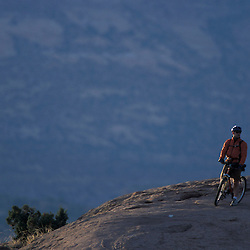 Moab, UT..Mountain biking on the Moab Slickrock Bike Trail.  Navajo Sandstone.  BLM land.  La Sal Mountains in background.