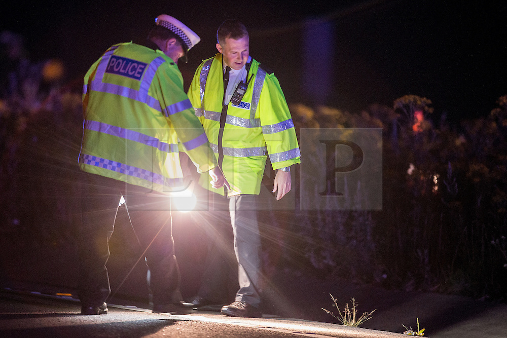 © Licensed to London News Pictures . 21/07/2014 . Nottinghamshire , UK . Police examine the slip road for evidence . Police , fire crew and ambulances on the A1 road in Ranby yesterday morning (21st July 2014) following a fatal multi vehicle accident . Leroy and Sheila Carrington (aged 68 and 58) died at the scene when the Peugot 206 they were driving collided with a Vauxhall Astra . Roderick Franks (58) , who was a passenger in the Astra , died in hospital , following the crash . The road was closed in both directions whilst police investigated the scene .  Photo credit : Joel Goodman/LNP