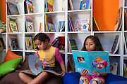 Giovana Lima do Rosa (left) and Ketlin Raissa Azevedo Trindade  (right) sit on colourful cushions reading books in the community library, Biblioteca Comunitaria do Arquipelago, Porte Alegre, Brazil. <br /> <br /> Cirandar is working in partnership with  C&A and C&A Instituto to implement a network of Community Libraries in eight communities of Porto Alegre.