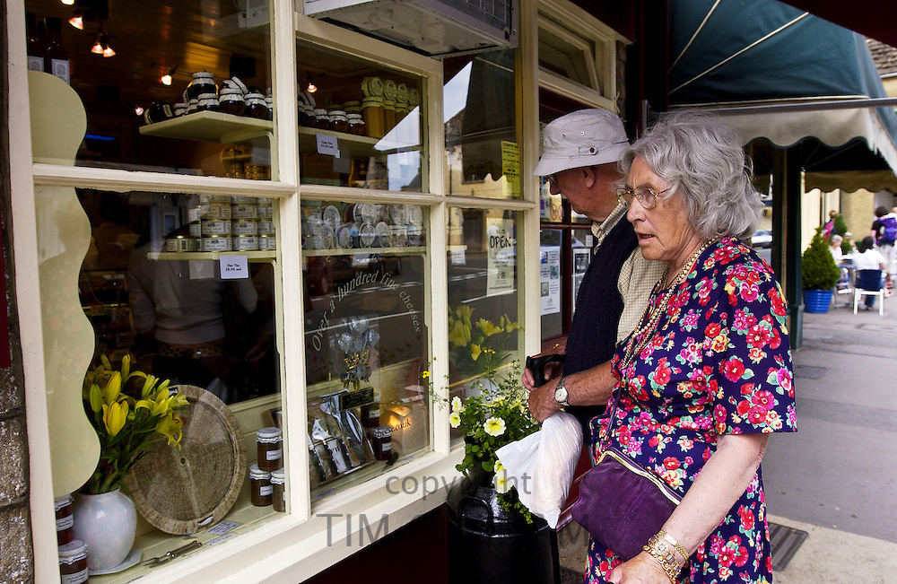 Elderly couple look in a shop window, Tetbury, England
