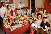 (MODEL RELEASED IMAGE). The Fernandez family in the kitchen of their San Antonio, Texas home with a week's worth of food. Lawrence, 31, and wife Diana, 35, standing, and Diana's mother, Alejandrina Cepeda, 58, sitting with her grandchildren Brian, 5, and Brianna, 4. Cooking methods: electric stove, microwave, toaster oven, outdoor BBQ. Food preservation: refrigerator-freezer. Favorite foods? Diana: shrimp with Alfredo sauce. Lawrence: barbecue ribs. Brian and Brianna: pizza. Alejandrina: chicken mole. /// The Fernandez family is one of the thirty families featured in the book Hungry Planet: What the World Eats (p. 270). Food expenditure for one week: $242.48 USD. (Please refer to Hungry Planet book p. 271 for the family's detailed food list.)