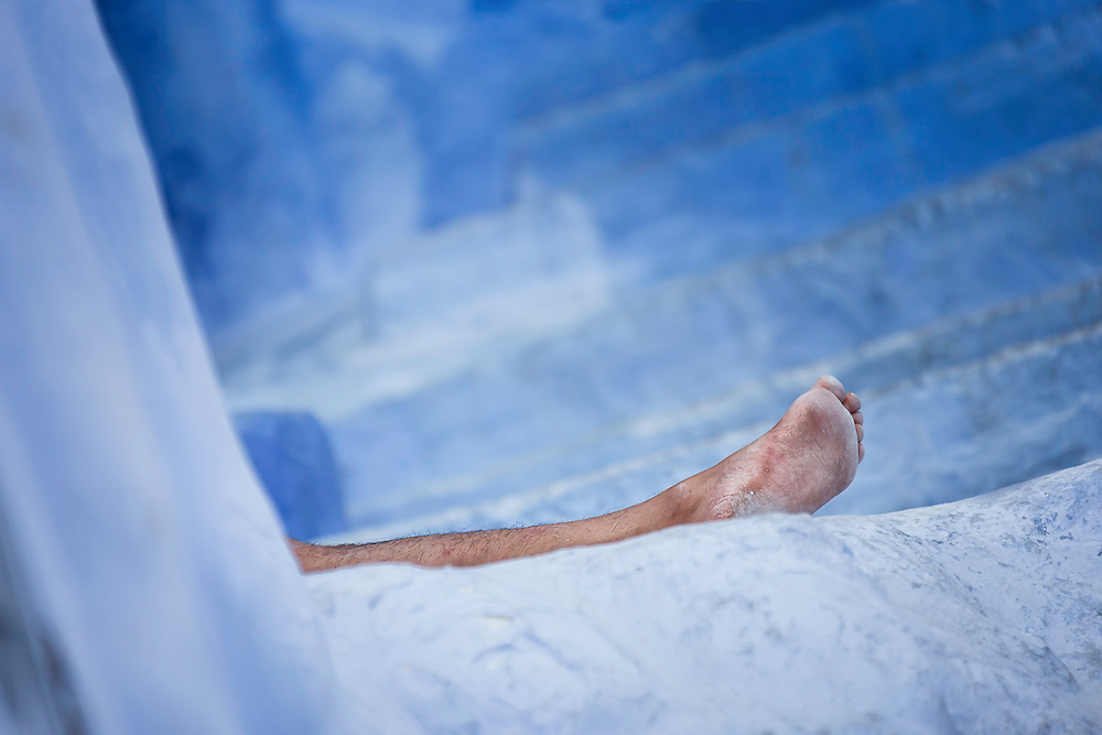 Naked leg of a man resting in front of his house in the medina of Chefchaouen, Morocco.
