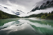 Mist slowly lifts from the forests and mountains surrounding Diablo Lake, an artificial reservoir formed by Diablo Dam in the heart of North Cascades National Park, Washington.