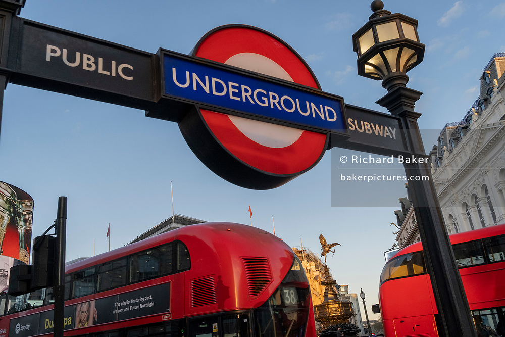 A low-angle view of London buses passing the Eros statue and an entrance to the Underground station at Piccadilly Circus in the West End, on 6th November 2020, in London, England.