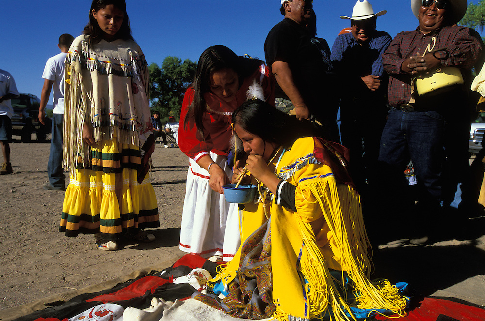 An Apache girl drinks water through a straw at her Sunrise Dance, a frist menstruation rite,  on the San Carlos Apache Indian Reservation in Arizona, USA.  Behind the girl, who is dressed in buckskin clothes, the medicine man and his helpers, who sing and beat their drums during the dance, are having a rest. The Sunrise Dance is held during the summer, within one year after the girl has had her first menstruation, and lasts for four days. The ceremony is an enactment of the Apache creation myth and during the rites the girl 'becomes' Changing Woman, a mythical female figure, and comes into possession of her healing powers. The rites are also supposed to prepare the girl for adulthood and to give her a long and healthy life without material wants.