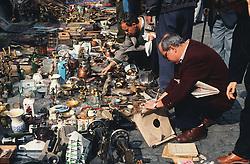 Rastro flea market in Madrid with men browsing the bricabrac,