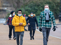 © Licensed to London News Pictures. 01/02/2021. London, UK. Members of the public in masks walk through Hyde Park in London as Sage experts urge the government to encourage wearing face masks outside to help reduce the spread of the more infectious Covid-19 mutations which are spreading throughout the UK. Today, door to door testing is to be carried out in Surrey after two people tested positive for the South African Covid-19 variant with no links to South Africa. Photo credit: Alex Lentati/LNP