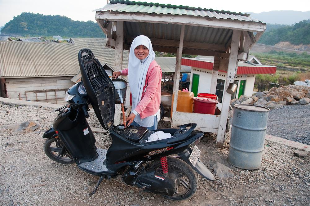 Indonesia, Sumatra, Aceh. Young Muslim girl fills her motor bike before heading to school.
